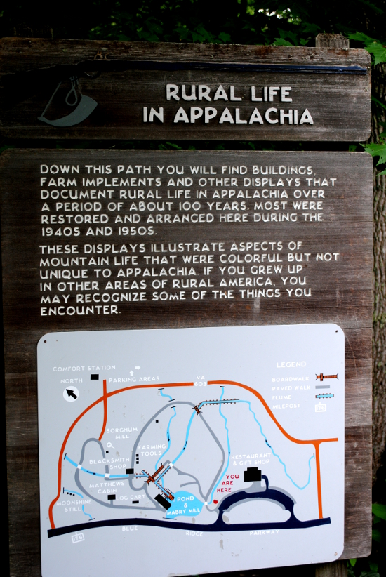Plaque reads: Down this path you will find buildings, farm implements and other displays that document rural life in Appalachia over a period of about 100 years. Most were restored and arranged here during the 1940s and 1950s. These displays illustrate aspects of mountain life that were colorful but not unique to Appalachia. If you grew up in other areas of rural America, you may recoginze some of the things you encounter.