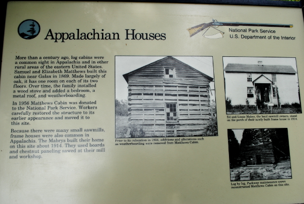 Plaque reads: More than a century ago, log cabins were a common sight in Appalachia and in other rural areas of the eastern United States. Samual and Elizabeth Matthews built this cabin near Galax in 1869. Made largely of oak, it has one room on each of its two floors. Over time, the family installed a wood stove and added a bedroom, a metal roof, and weatherboarding. In 1956 Matthews Cabin was donated to the National Parks Service. Workers carefully restored the structure to its earlier appearance and moved it to this site. Because there were many small sawmills, frame houses were also common in Appalachia. The Mabrys built their home on this site about 1914. They used boards and chestnut paneling sawed at their mill and workshop.