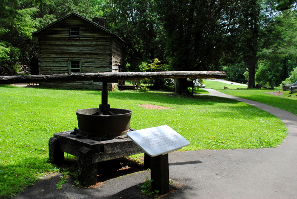 """Plaque reads: Bark Mill Simon the Tanner used this horse-powered machine to grind oak and hemlock bark for tanning. Mixed with water this ground bard produced """"bark liquor"""" for tanning hides."""