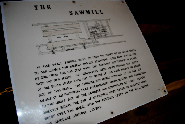Plaque reads: In this small sawmill Uncle Ed used the power of his water wheel to saw lumber for himself and his neighbors. Logs were rolled, one by one, from the log deck onto the carriage and