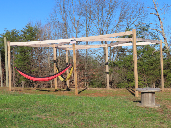 A wooden structure built to attach hammocks out on the lawn in the sunshine.
