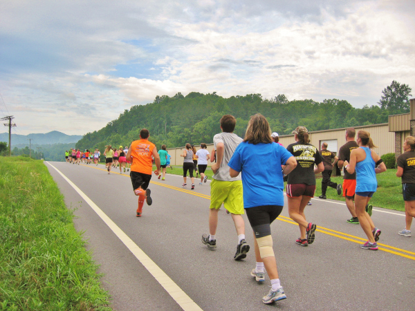 Runners starting out on the Covered Bridge 5K. Photo shows the race on a paved two lane road with the Blue Ridge in the distance.