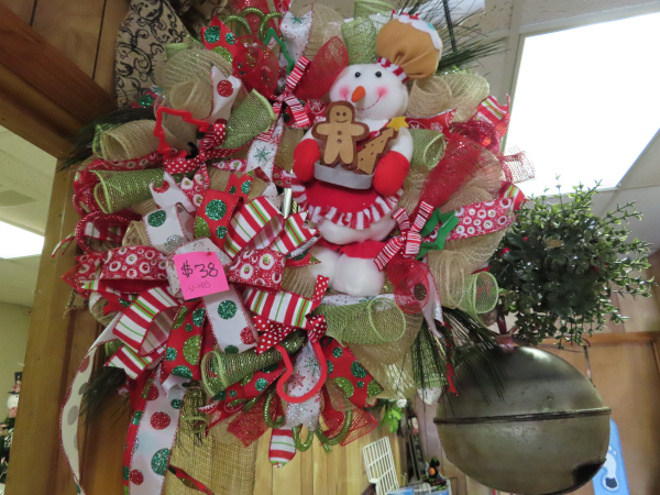 An elaborate Christmas wreath with a snow person carrying gingerbread cookies