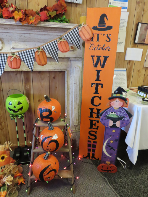 Halloween Decorations - painted pumpkins and a tall placard saying It's October Witches